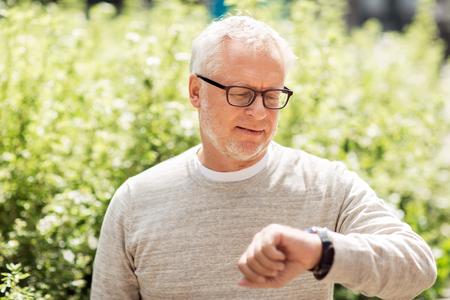 senior man checking time on his wristwatch Stock Photo