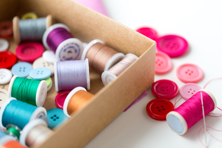 Spirale: box with thread spools and sewing buttons on table