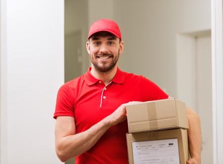Hombre de entrega con las cajas de paquetería en el pasillo Foto de archivo - 78749103