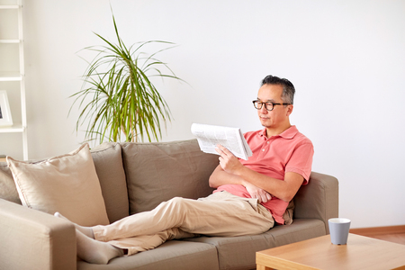 happy man in glasses reading newspaper at home Imagens