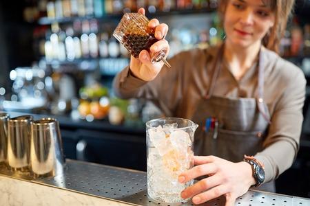 woman bartender preparing cocktail at bar