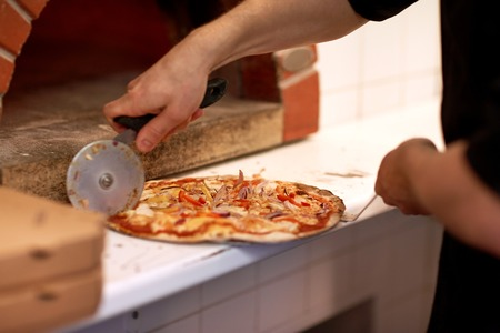 cutter: cook hands cutting pizza to pieces at pizzeria