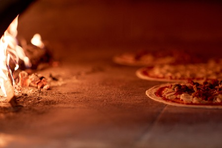 hotbed: pizza baking in oven at pizzeria