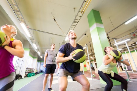group of people with medicine ball training in gym Stock Photo