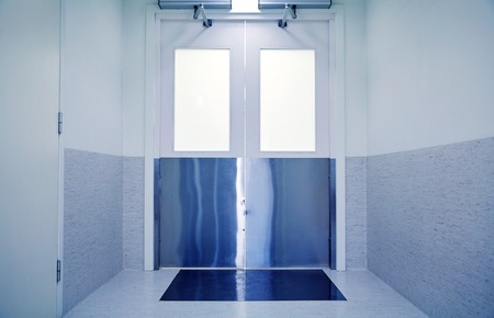 medicine, science, health care, emergency and interior concept - doors at hospital or laboratory corridor