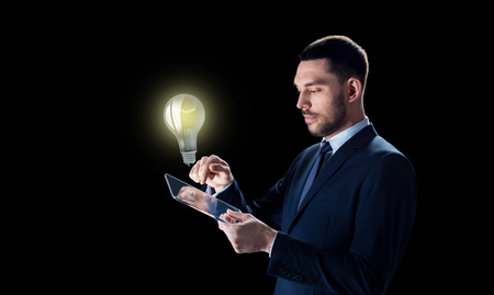 business, people, startup idea, inspiration and modern technology concept - businessman in suit working with transparent tablet pc computer and lightbulb over black background