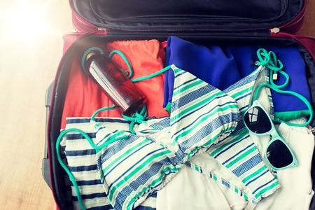 summer vacation, travel, tourism and objects concept - close up of travel bag with beach clothes, sunglasses and sunscreen 版權商用圖片