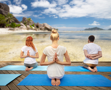 group of people making yoga exercises over beach Stock Photo