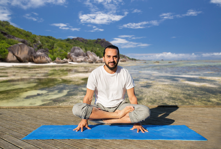 man making yoga in scale pose outdoors Stock Photo