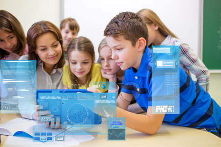 education, elementary school, learning, technology and people concept - group of kids with teacher looking to tablet pc computer in classroom and virtual screen projection photo