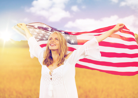 country, patriotism, independence day and people concept - happy smiling young woman in white dress with national american flag on cereal field Stock Photo