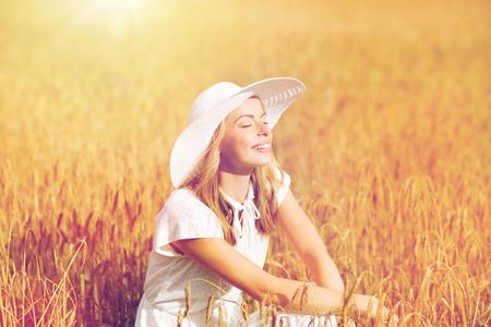 Natuur, zomervakantie, vakantie en mensen concept - gelukkige jonge vrouw in witte jurk en zonnehoed genieten van zon op graangebied Stockfoto