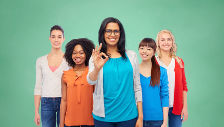 education, diversity and people concept - international group of happy smiling different women showing ok hand sign over green school chalk board background