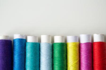 needlework, craft, sewing and tailoring concept - row of colorful thread spools on table Stock Photo