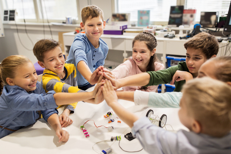 education, children, technology, science and people concept - group of happy kids building robots and making high five gesture at robotics school Imagens - 78954623