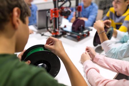 教育、子供、技術、科学、人々 のコンセプト - ロボット学校の授業で 3 d プリンターとフィラメントのスプールの子どもたちのグループ 写真素材