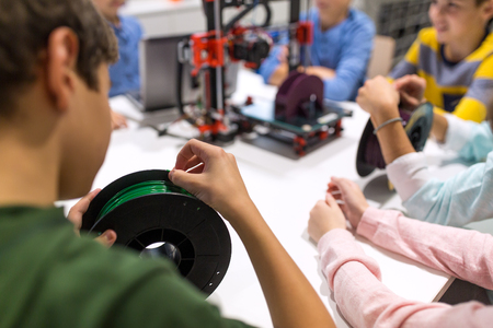 education, children, technology, science and people concept - group of kids with 3d printer and filament spool at robotics school lesson Stock Photo - 78954632