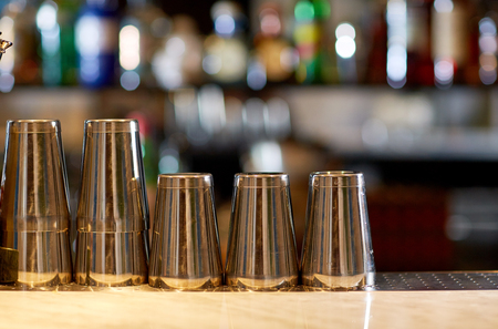 multiple objects: stainless steel shakers on bar counter