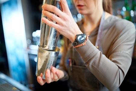 close up of bartender with cocktail shaker at bar 版權商用圖片