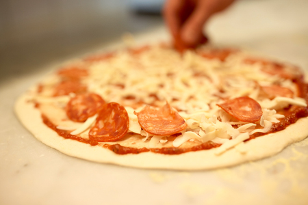 cook hands adding salami to pizza at pizzeria