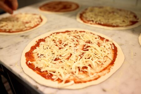 raw pizza with grated cheese on table at pizzeria Stock Photo