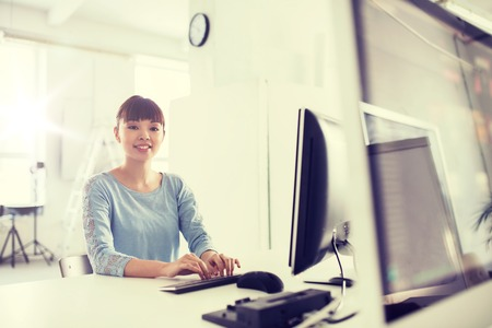 happy asian people: business, startup, education and people concept - happy young asian woman with computer working at office Stock Photo