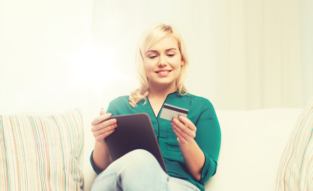 emoney: people, internet bank, online shopping, technology and e-money concept - happy young woman sitting on sofa with tablet pc computer and credit card at home Stock Photo