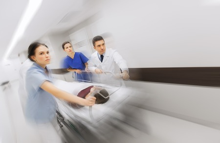 health care, reanimation and medicine concept - group of medics or doctors carrying unconscious woman patient on hospital gurney to emergency (motion blur effect)