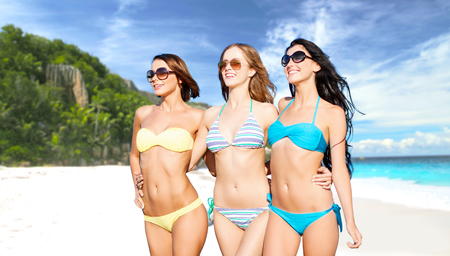 summer holidays, travel, people and vacation concept - happy smiling young women in bikinis and shades over exotic tropical beach background