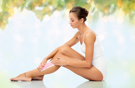 beauty, hair removal and people concept - beautiful woman applying depilatory wax strip to her leg skin over natural green background and lights