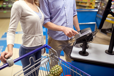 shopping, sale, payment, consumerism and people concept - couple with bank card buying food at grocery store or supermarket self-checkout Banque d'images