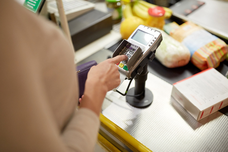 shopping, sale, consumerism and people concept - woman buying food at grocery store or supermarket cash register and entering pin code