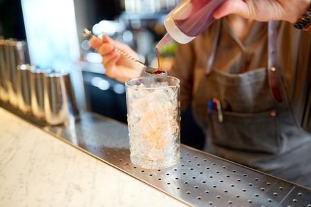 bartender with cocktail stirrer and glass at bar 版權商用圖片