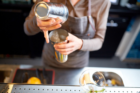 woman bartender with cocktail shaker at bar