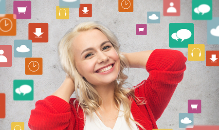 people, multimedia and technology concept - happy smiling young woman in red cardigan Stock Photo