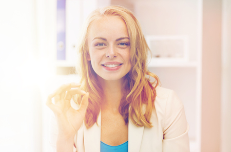 business, gesture, success, startup and people concept - happy businesswoman showing ok sign at office Stock Photo