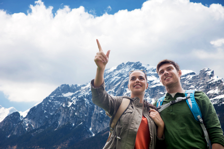 travel, tourism and hike concept - smiling couple with backpacks hiking or traveling over alps mountains background
