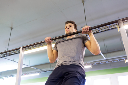 sport, fitness and people concept - man exercising and doing pull-ups on horizontal bar in gym