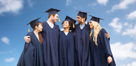 education, graduation and people concept - group of happy international students in mortar boards and bachelor gowns over blue sky and clouds background Stock Photo