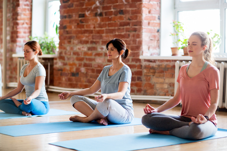 fitness, people and healthy lifestyle concept - group of women meditating in lotus pose at yoga studio Foto de archivo