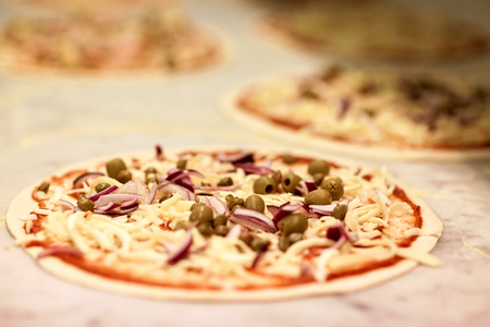 food, culinary, italian cuisine and cooking concept - raw pizza with grated cheese on table at pizzeria