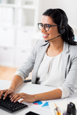 communication, business, people and technology concept - smiling businesswoman or helpline operator with headset typing on keyboard at office