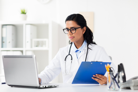 healthcare, technology people and medicine concept - female doctor in white coat with laptop computer and clipboard at hospital