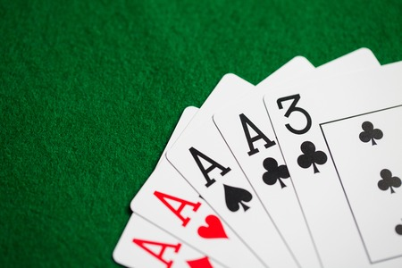 casino, gambling, games of chance, hazard and entertainment concept - poker hand of playing cards on green cloth Stock Photo