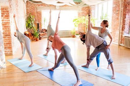 fitness, sport en gezonde levensstijl concept - groep mensen met personal trainer doen yoga oefeningen op matten in de sportschool of studio