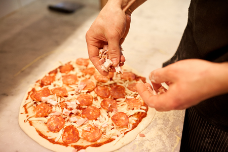 pizza maker: food, culinary, italian cuisine, people and cooking concept - cook hands adding ham to salami pizza at pizzeria
