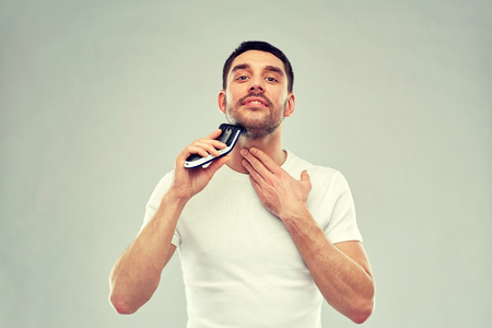 smiling man shaving beard with trimmer over gray