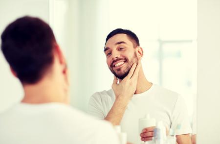 metrosexual: happy man applying aftershave at bathroom mirror