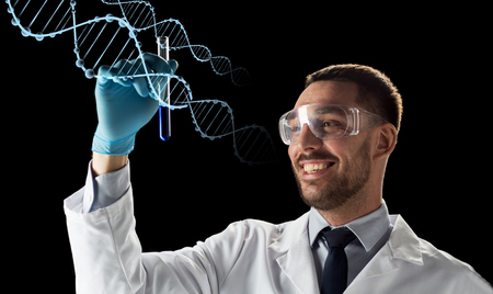 smiling scientist in safety glasses with test tube