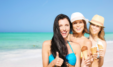 group of happy young women with ice cream on beach photo